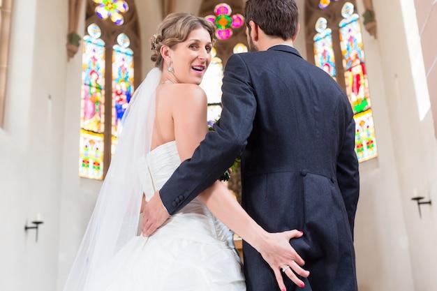 花嫁の教会での結婚式で新郎のお尻を掴んで Premium写真
