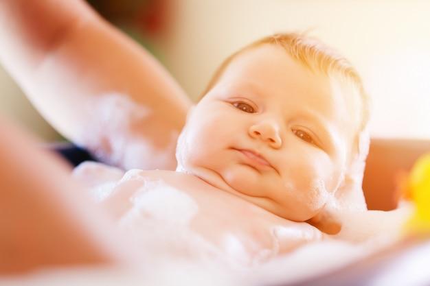 母はバスタブで赤ちゃんを浴びています。 Premium写真