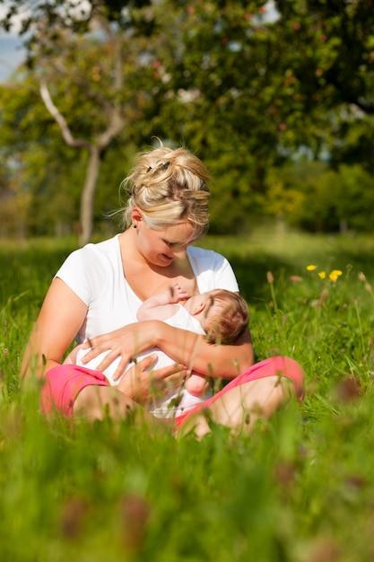 牧草地で母親看護赤ちゃん Premium写真