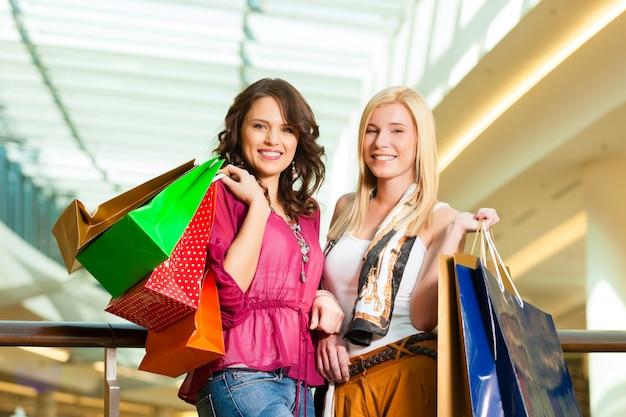ショッピングモールでバッグと一緒に買い物をする女性 Premium写真