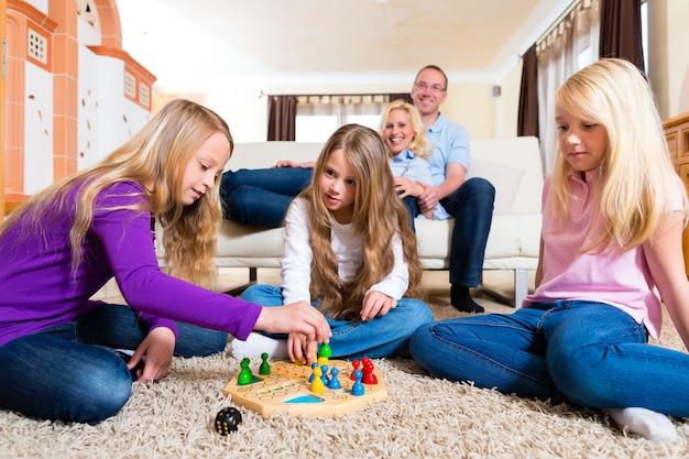 Семья играет в настольную игру дома Premium Фотографии