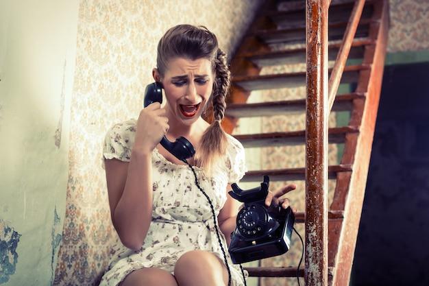 Женщина сидит на лестнице и плачет по телефону Premium Фотографии