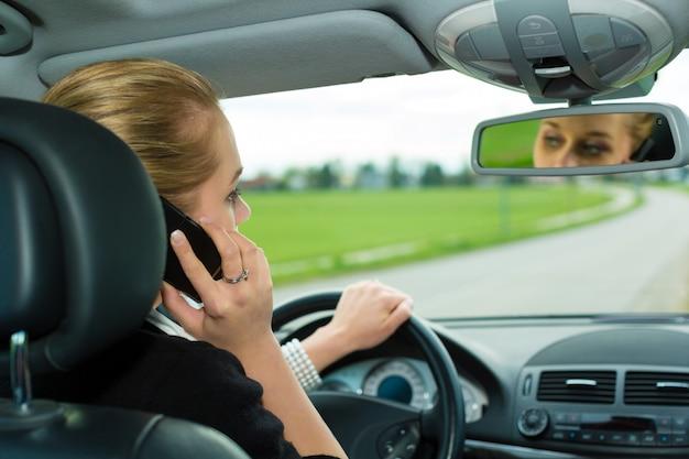 車の中で電話を持つ若い女性 Premium写真