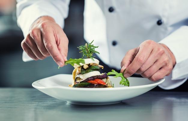 Шеф-повар в ресторане гарнирует овощное блюдо Premium Фотографии