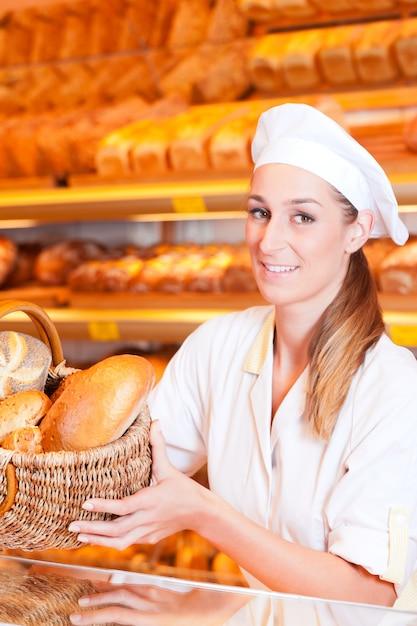 彼女のパン屋でパンを売る女性のパン屋 Premium写真