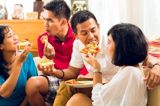 Азиатские люди едят пиццу на вечеринке Premium Фотографии