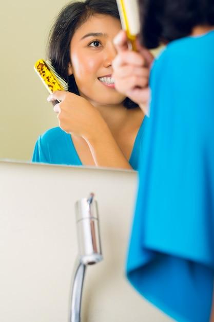 バスルームの鏡で髪をとかすアジアの女性 Premium写真