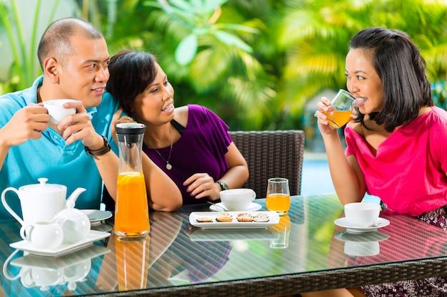 ホームポーチでコーヒーを飲んでいるアジアの友人 Premium写真