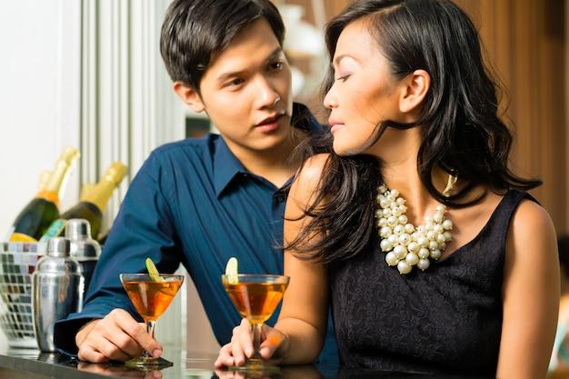アジアの男と女のバーでカクテル Premium写真