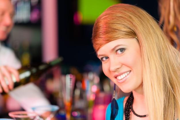 クラブやバーでシャンパンを飲む若い女性 Premium写真