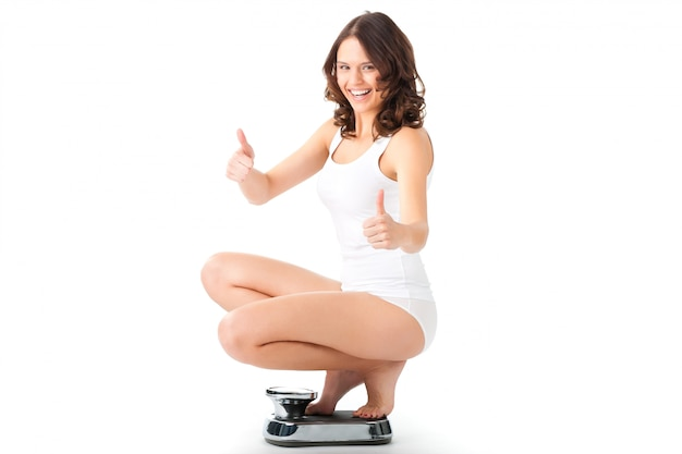 スケールで彼女のおしりの上に座っている若い女性 Premium写真