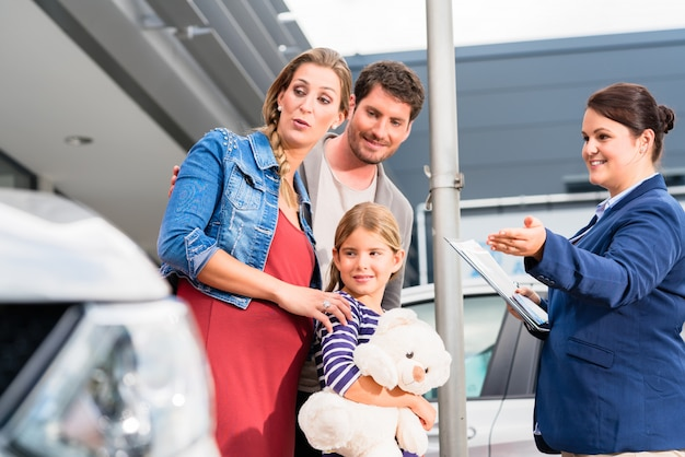 自動車を買うことについて家族に助言する自動車ディーラー Premium写真