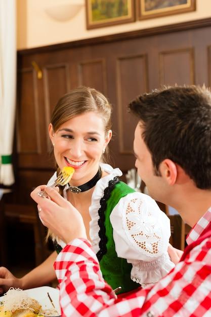 Люди в традиционном баварском трахте едят в ресторане или пабе Premium Фотографии