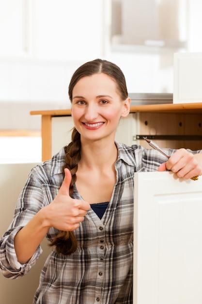 若い女性は食器棚を組み立てています Premium写真