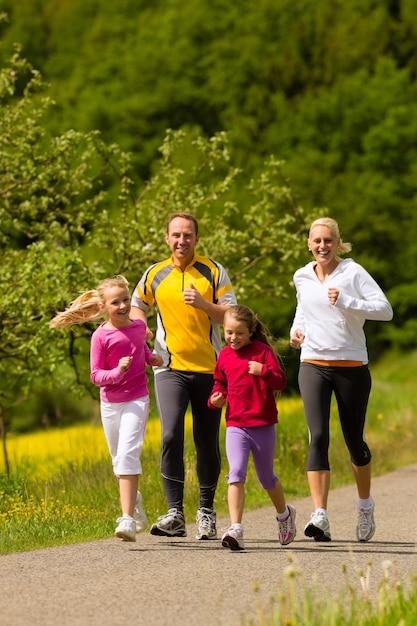 スポーツのための牧草地で実行されている家族 Premium写真