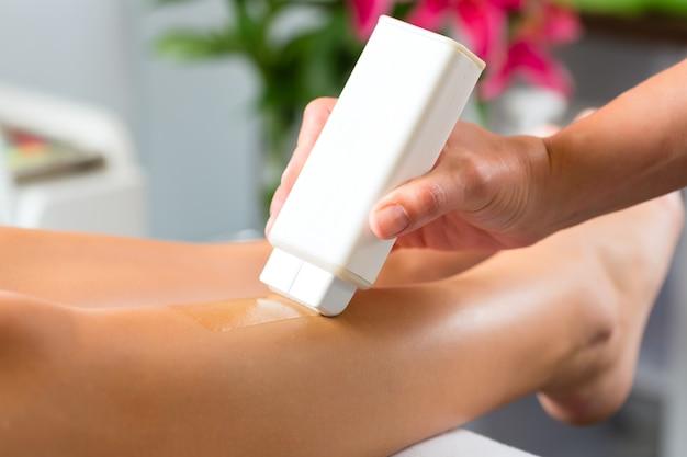 足のワックスを取得するスパの女性 Premium写真
