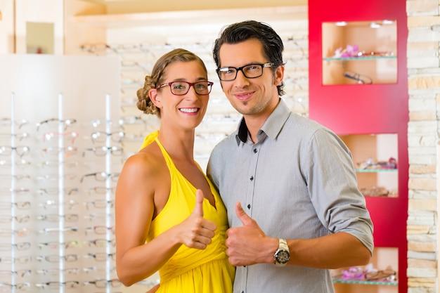 眼鏡の眼鏡屋で若いカップル Premium写真