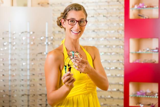 眼鏡の眼鏡屋で若い女性 Premium写真