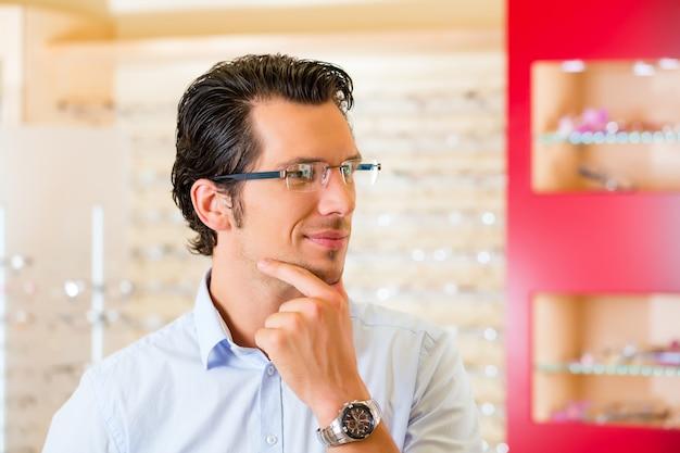 眼鏡の眼鏡屋で若い男 Premium写真