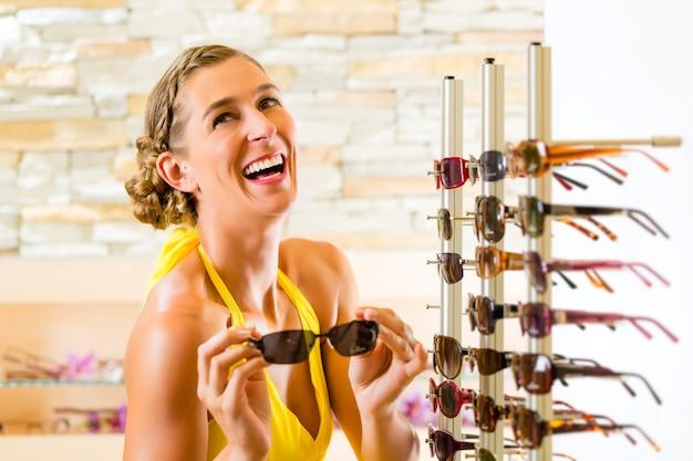 メガネのショッピングサングラスで若い女性 Premium写真