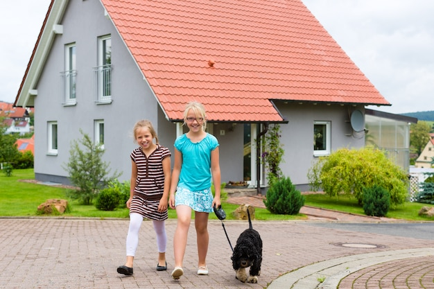Две девочки или дети гуляют с собакой Premium Фотографии