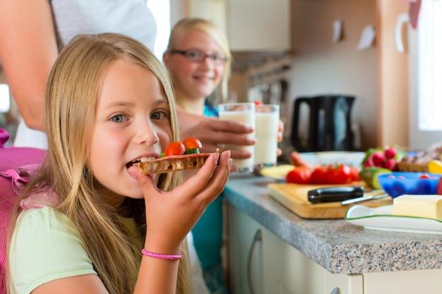 Семья, мама готовит завтрак для школы Premium Фотографии