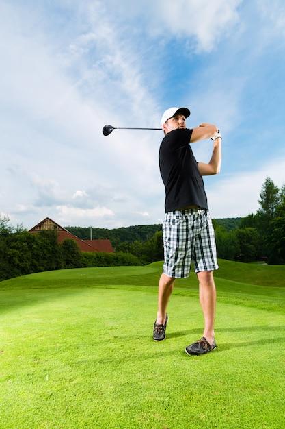 ゴルフスイングを行うコースの若いゴルフプレーヤー Premium写真