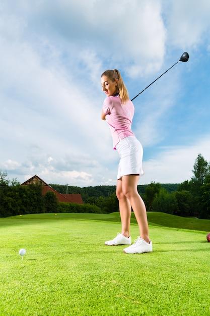 ゴルフスイングを行うコースの若い女性ゴルフプレーヤー Premium写真