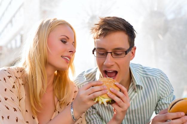 カップルは空腹で、休憩でハンバーガーを食べています Premium写真