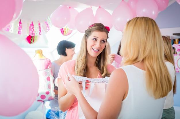 ベビーシャワーで妊娠中の友人に贈り物を与える女性 Premium写真