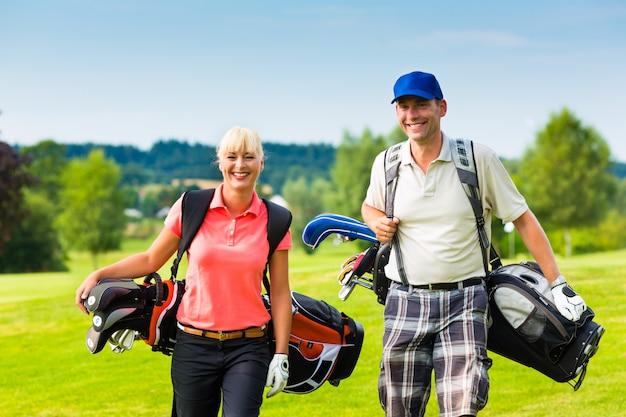 コースでゴルフをする若い陽気なカップル Premium写真