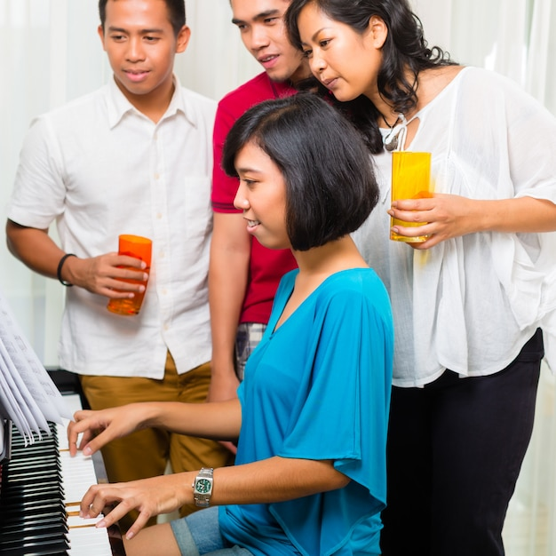 ピアノで一緒に座っているアジアの人々 Premium写真