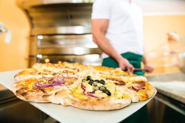 Мужчина выталкивает готовую пиццу из духовки Premium Фотографии