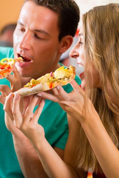 Мужчина и женщина едят пиццу Premium Фотографии