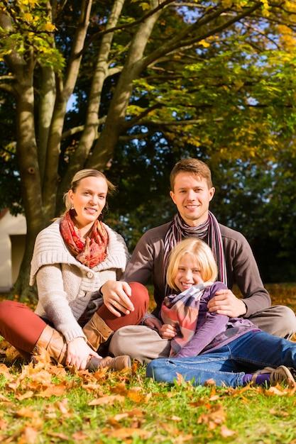 秋の草の上に座って屋外の幸せな家族 Premium写真