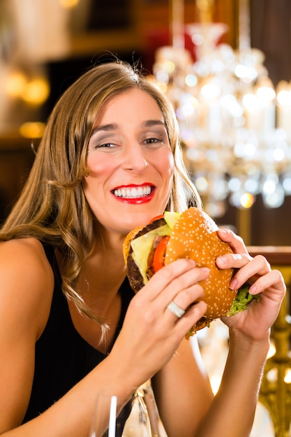若い女性の高級レストランはハンバーガーを食べ、彼女は不適切に動作します Premium写真