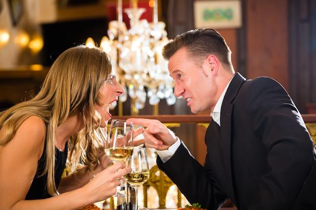 カップルは、彼らが怒って叫んでいるロマンチックなデートの高級レストランで口論をしている、大きなシャンデリア Premium写真