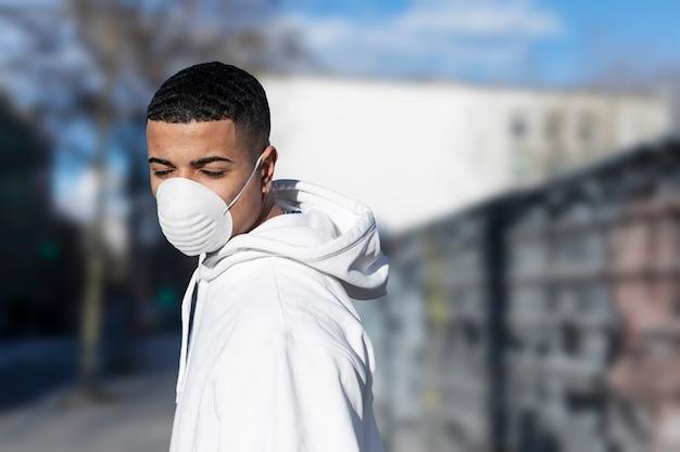 Закройте вверх по портрету молодого мужчины нося защитную лицевую маску против заразных инфекционных заболеваний и как защита от гриппа или коронавируса в общественном месте. Premium Фотографии