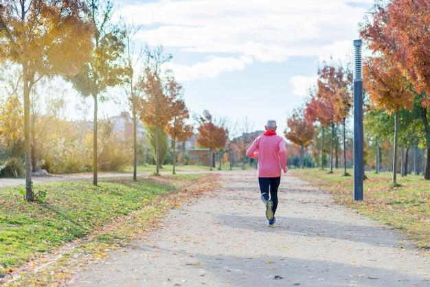 黒と緑に身を包んだ年配の男性が公園で走っています。 Premium写真