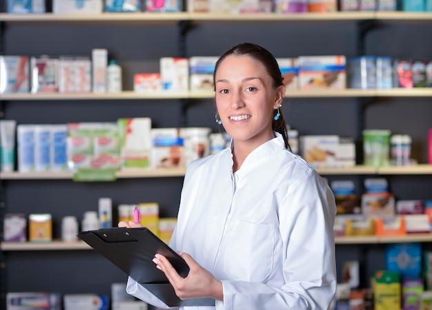 Красивая фармацевт, используя блокнот в аптеке Premium Фотографии
