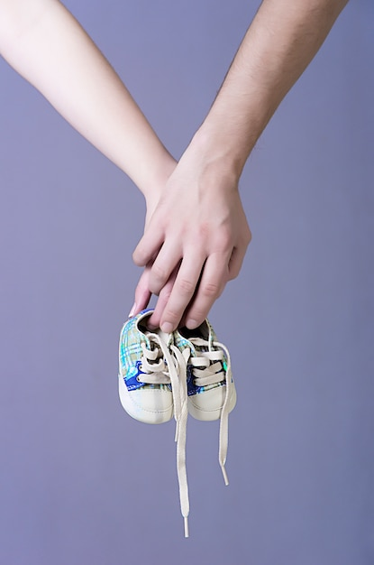 Руки ожидающих родителей с парой кроссовок для мальчиков Premium Фотографии