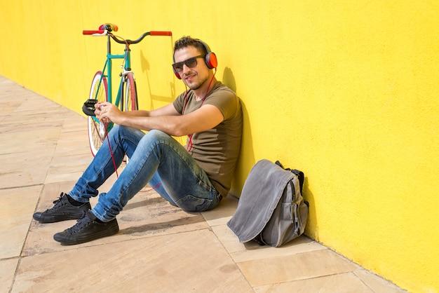床にリラックスして音楽を聴くのサングラスをかけている若い男。彼のコンピューターと黄色の壁に座っています。 Premium写真