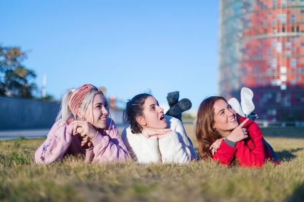 草の上に横たわって一緒に笑っている美しい女の子の小グループ Premium写真