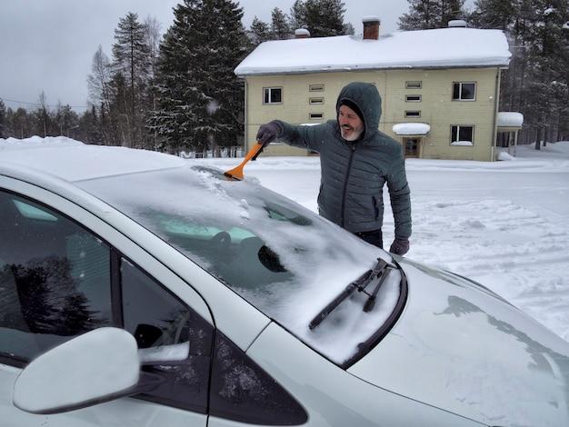 ブラシで車のフロントガラスから雪を掃除する一人の男 Premium写真
