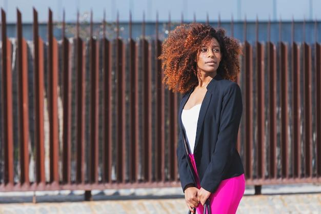 Вид спереди молодой красивой кудрявой женщины носить элегантную одежду и сумочку, стоя на улице в солнечный день Premium Фотографии