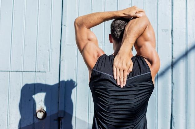 Молодой человек растягивается на фоне голубой стены после тренировки Premium Фотографии