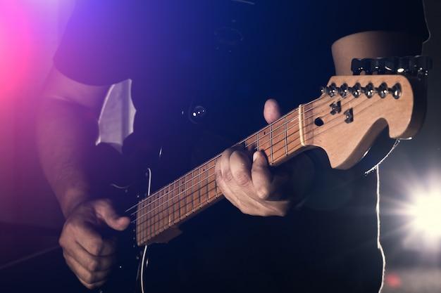 Мужчина держит электрогитару на черном фоне Premium Фотографии