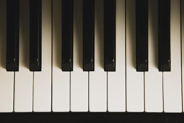 照明と影を持つピアノキーボードの平面図です。 Premium写真