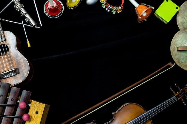 黒の背景にバイオリンギターとウクレレの打楽器のトップビュー Premium写真