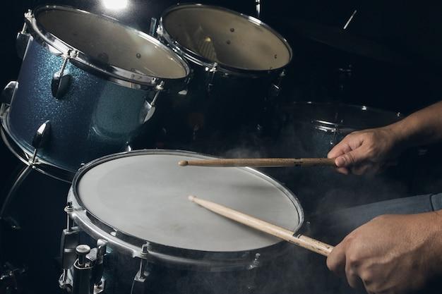 男は暗い光の背景に設定されたドラムを演奏しています。 Premium写真